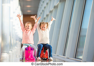 Adorable little girls having fun in airport sitting on suitcase waiting for boarding