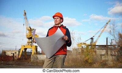 Portrait man builder in orange helmet looks instruments...