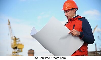 man portrait architect builder in orange helmet looks...