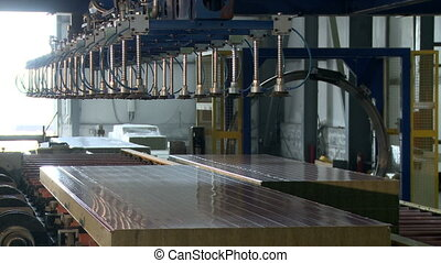 Workers controls operation of conveyor at production shop