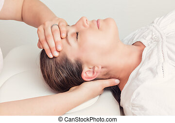 Osteopathy - lying woman gets treatment at the head