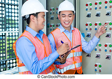 Asian technicians at panel on construction site - Asian...