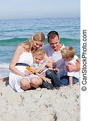 Smiling mother with her family holding sunscreen at the...