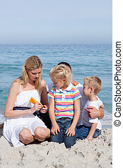 Attentive mother holding sunscreen at the beach with her...