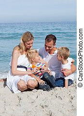 Caring mother with her family holding sunscreen at the beach...