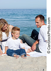 Happy parents with their son sitting on the sand at the...
