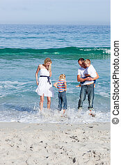Cheerful family having fun at the beach - Cheerful family...