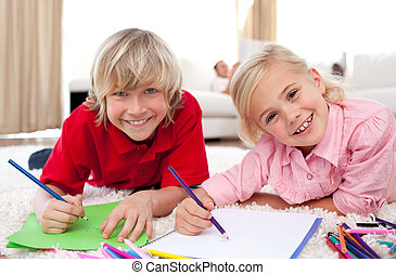 Smiling children drawing lying on the floor in the...