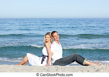Smiling couple sitting on the sand