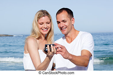 Intimate couple holding a camera standing on the sand
