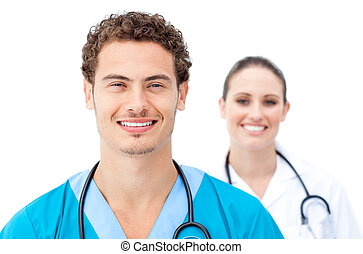 Self-assured doctors standing in a row against a white...