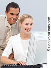 Joyful manager helping a businesswoman with her computer