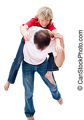 Father giving his son piggyback ride against a white...