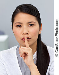 Attractive businesswoman asking for a silence in a office