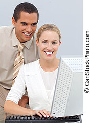 Positive manager helping a businesswoman with her computer