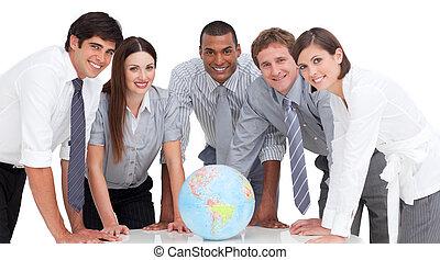 Confident business team standing around a terrestrial globe...