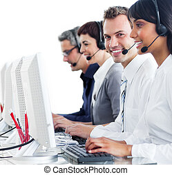 Blissful customer reprensatives working at a computer -...