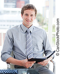 Young male executive looking at his agenda in his office