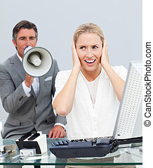 Charismatic manager yelling through a megaphone in his colleague\'s ears in the office