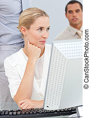 Pensive blond woman working at a computer