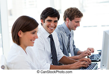Positive business people working at computers in the office