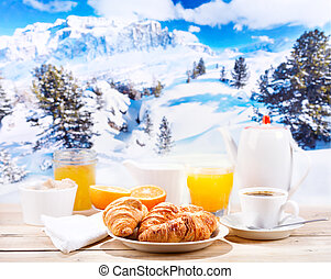 breakfast with coffee and croissants over winter landscape