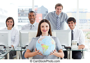 Confident businesswoman holding a terrestrial globe in front...