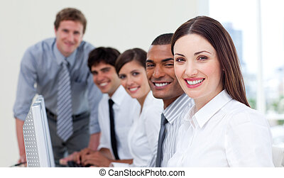 Cheerful business team working at computers in a company