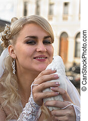 Bride the blond and white dove in hands Young woman