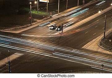 Two cars at a crossroads wait at night a green signal of a...