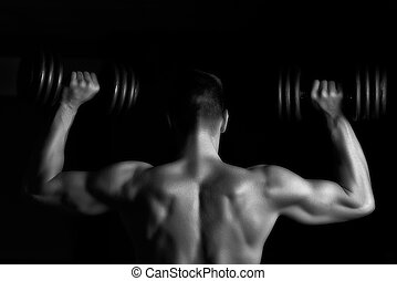 Handsome young muscular man lifting weights over dark...