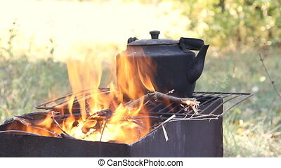 old smoked teapot on the campfire - Black old smoked teapot...