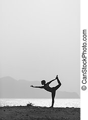 Woman meditating in yoga pose silhouette
