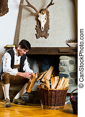 Young man in a hunters cabin or alpine hut - Young man in a...