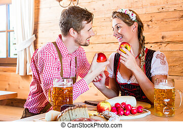 Couple having dinner at mountain hut in alps drinking beer...