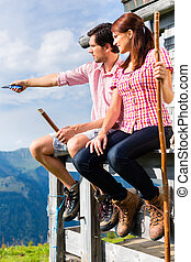 Alps - Man and woman sitting at cabin in tirol - Hiking -...