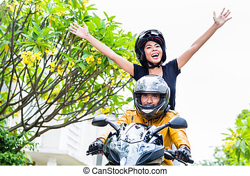 Indonesian woman feeling free on motorcycle stretching her...