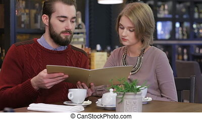Couple chooses the menu. Celebrating a Valentine's Day at a...