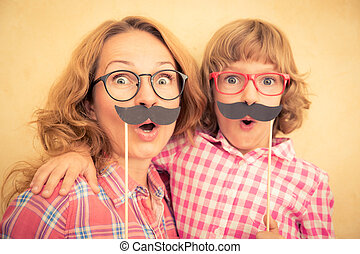 Mother and child with fake mustache Happy family playing in...