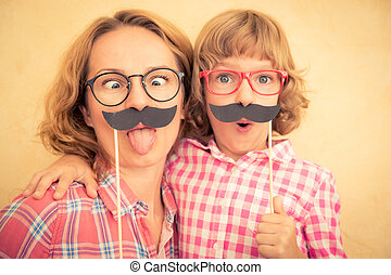 Mother and child with fake mustache. Happy family playing in...