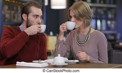 Portrait of young beautiful couple in love having coffee in beautiful cafe