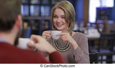 Young couple sitting in a cafe drinking coffee and tea....