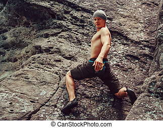 Young man climbing on stone rock, bouldering - Free climber...