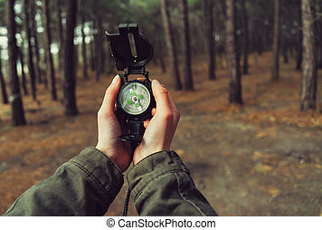 POV of hands with a compass - Hiker woman holding a compass...