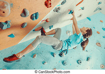 Young woman training in climbing gym - Sporty young woman...