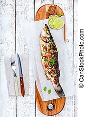 baked fish sea bass with lime and parsley on a board