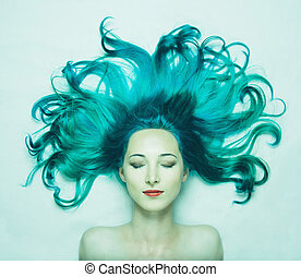 Beautiful young woman with long hair of turquoise color -...