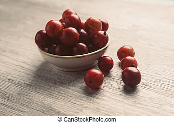Fresh ripe red gooseberries in a bowl on wooden background