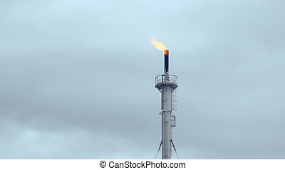 refinery fire gas torch over blue sky