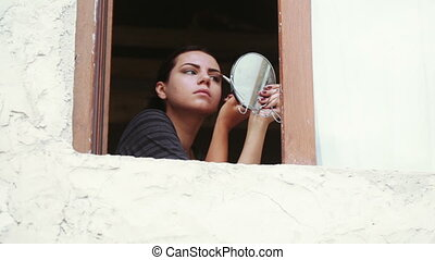 Girl at window does makeup - In open window Girl doing...